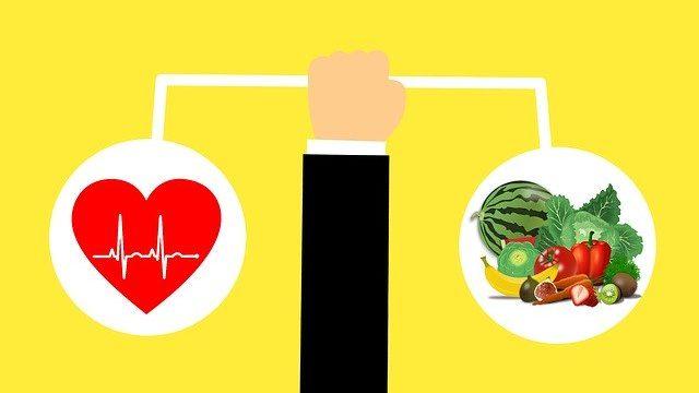 心臓と健康的な野菜の天秤